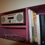 A radio and a bookshelf with books and CD.s.