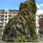 Monument in the format of a dog, covered with flowers at the entrance of the Guggenheim Bilbao