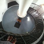 The iron lighthouse stairway, looking down. The white enamelled tower walls gleaming.