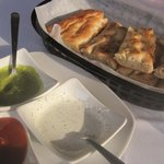 Afghan Naan (bread) with three dipping sauces.  We like the green coriander-based sauce the best