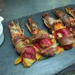 Pimientos de piquillos rellenos de pescado y gambas, envueltos con panceta y asados con su salsa