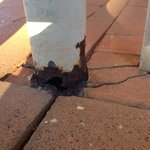 Rusty support pole for concrete walkway