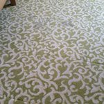 Stained carpeting with patchwork replacements.
