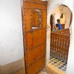 porte d'une chambre donnant sur escaliers et corridors