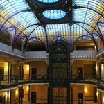 A view of the interior, the wrought iron elevator and the Tiffany glass ceiling