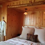 Cottage 3 - nice bed, knotty pine, robes, and soft lighting