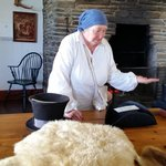 Summer volunteer in the Great Hall demonstrating how beaver pelts were used to make hats