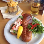 Noisy Lobster Roll with brioche bread and a side of chips.