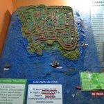 Maqueta de colonia colonial sofrendo ataque de barcos
