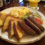 Breakfast: French toast, eggs, fruit, and sausage.