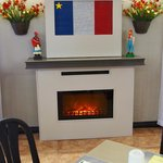 A small fireplace and strains of traditional French music playing add to the cozy ambiance here.