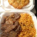 Bistec encebolla, arroz con gandules, and bacalaito