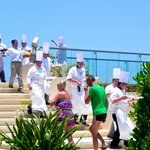 A parade of chefs bring out bites of food and drinks to pool area