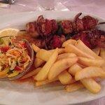 Souvlaki di maiale, servito con patatine e insalatina di peperoni