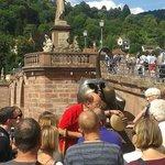 turista atendiendo explicación sobre el bronce del gato-mono