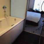 浴室。ガラスの外側にある障子のようなドアをスライドさせると室内のテレビを観ながらバスタブに浸かれます。