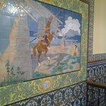 Una de las paredes muestra una cuadro de azulejos con la historia del Quijote y los molinos.