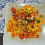 Ravioli relleno de salmón con salsa de tomate y gambas