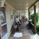 Partial view of the long wooden front porch for the rooms