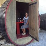 Tourist shot drinking wine in a barrel