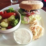 Burger with salad, coleslaw and dip.
