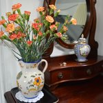 Flowers and a matching pitcher adorn the antique dresser .