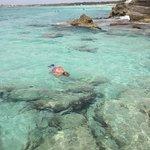 prachtig water, zonnen op de rotsen, iets verderop zandstrand