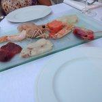 Antipasto di crudité di mare servito con salsa di soia, salsa agrodolce e salsa wasabi.