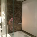 Bath with marble surround  and rain shower