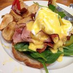 Eggs Benedict with heirloom tomatoes, spinach, applewood bacon, ham, on sourdough bread.