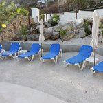 Sandy area in front of pool with lounge chairs, parasols...