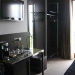 angolo di camera con porta abiti, tv e tavolo con macchina del caffè