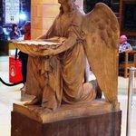 An Angel holding a baptism font