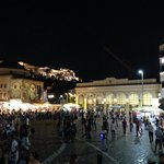 Monastiraki vibrant square. Far above is the lighted Acropolis.