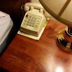 Old phone with wrong room number and scratched, old furniture