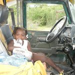 a little girl sits behind the wheel of an old land rover in crooked tree belize