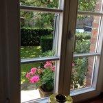Blick in den eigenen Garten mit Tischgarnitur und großem Sonnenschirm
