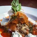 Merguez meatball sitting on sicilian couscous + moroccan spiced pomodoro sauce & whipped ricotta
