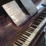 Piano antigo com partituras metálicas