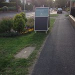 A board on council grass verge blocks vision when leaving car park