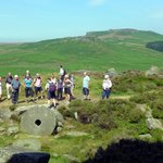 The Wednesday free guided walk pause by some millstones to admire the view of Carl Wark and Higg