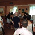 Lunga fila per il check-in con personale molto affaticato