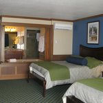 One of the beds in the room with the hot tub doors open