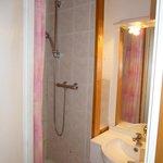 La minuscule douche avec ses traces de saleté dans les joints et son très agréable rideau...