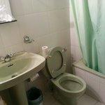 Cuarto de baño,  antiguo y con cortina en la bañera