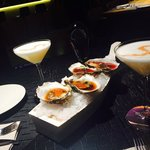 Amazing combination, oysters in ceviche sauce accompanied with Peruvian cocktail Pisco Sour