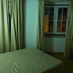 chambre avec lumière blafarde et rideau décroché