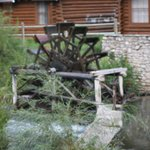 water wheel in stream behind cabin