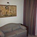 Sofá y mesa de café en la habitación, frente al escritorio y al lado del balcón.