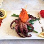 Oktopus im Ganzen auf lila Kartoffeln und marinierten Bohnen